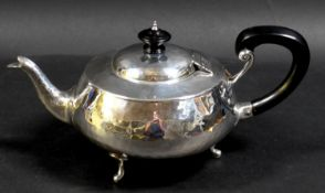An Arts & Crafts silver teapot, of compressed ovoid form, with all over hammered finish, ebonised