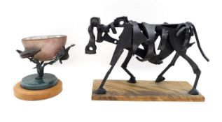 A modernist metal sculpture of a cow, constructed from mechanical parts and scrap on a simple wooden