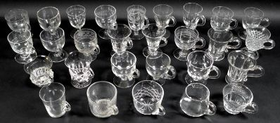 A collection of clear glass custard cups, jelly or syllabub cups, mostly Victorian and later,