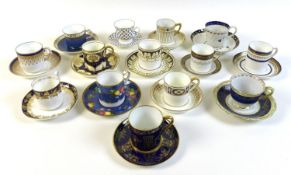 A group of fourteen coffee cans and saucers, in shades of blue, white and gold.
