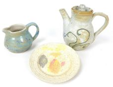A 20th century studio pottery coffee pot, the cream on biscuit textured ground decorated with sky