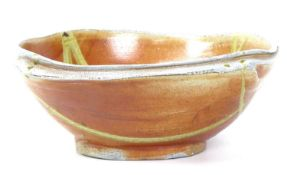 A large 20th century studio pottery bowl, of shaped circular form with orange and green glazed