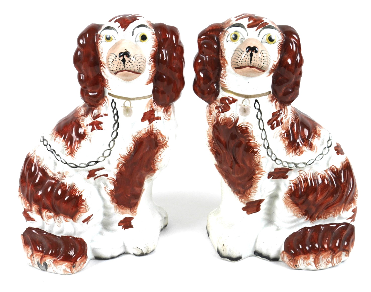 A pair of Victorian Staffordshire flatback fireside dogs, modelled as spaniels, each 25cm high. (2)