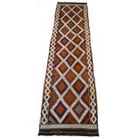 An old Suzni kelim runner, decorated with zoomorphic and foliate designs upon a red ground 295 by