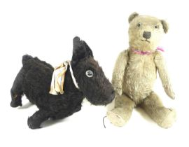 Two early 20th century soft toys, one a black dog, 23cm tall, the other a bear, 38cm tall. (2)