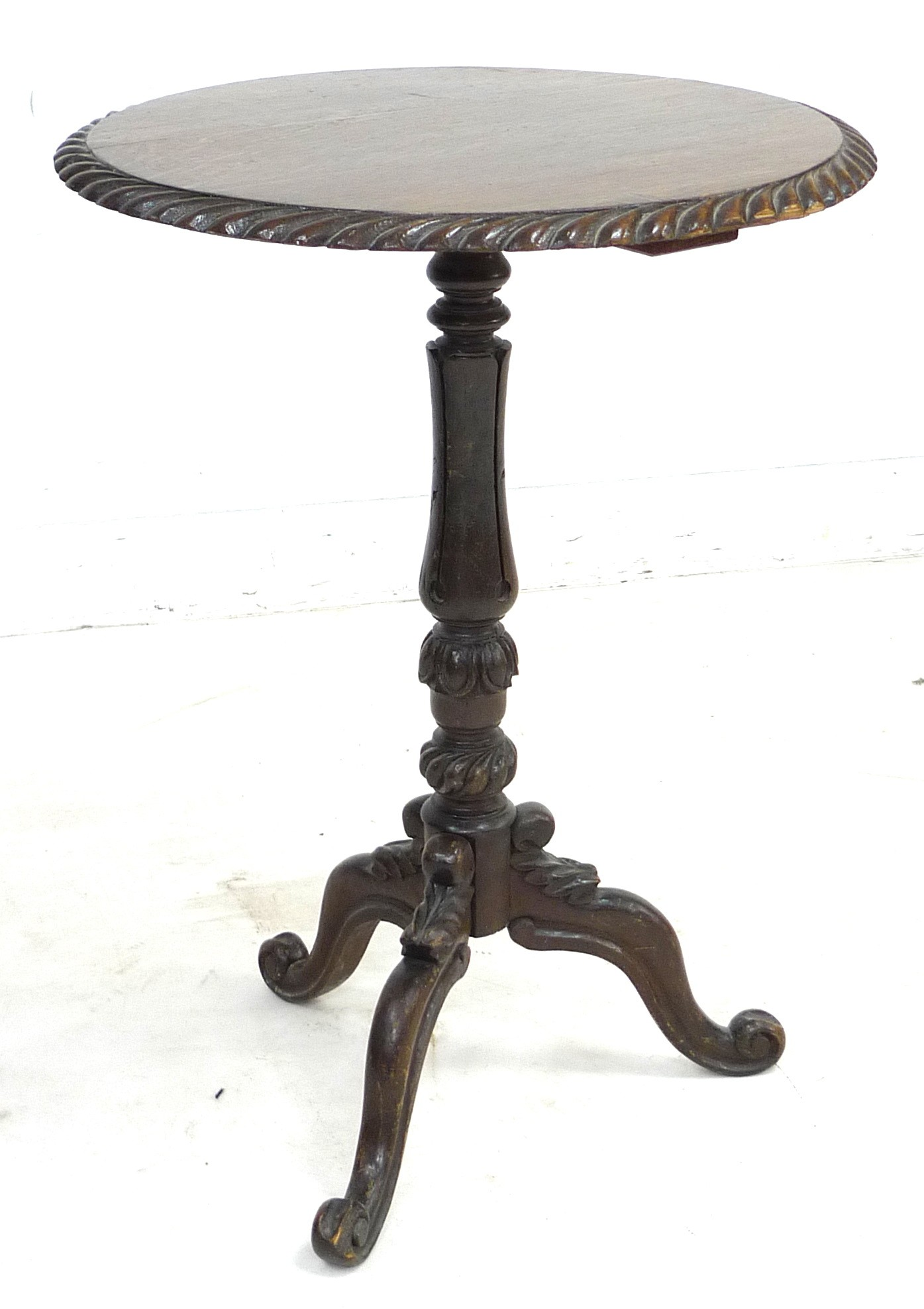 A late Victorian oak wine table, the circular surface with carved gadrooned edge, raised on a lappet