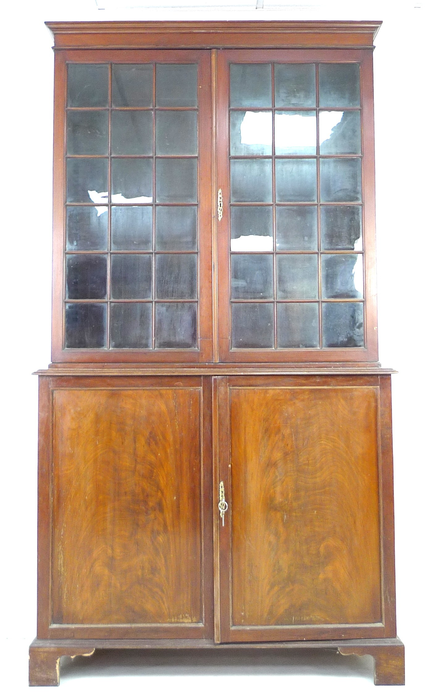 An Edwardian mahogany bookcase, with astragal glazed double doors, above a cupboard base, raised