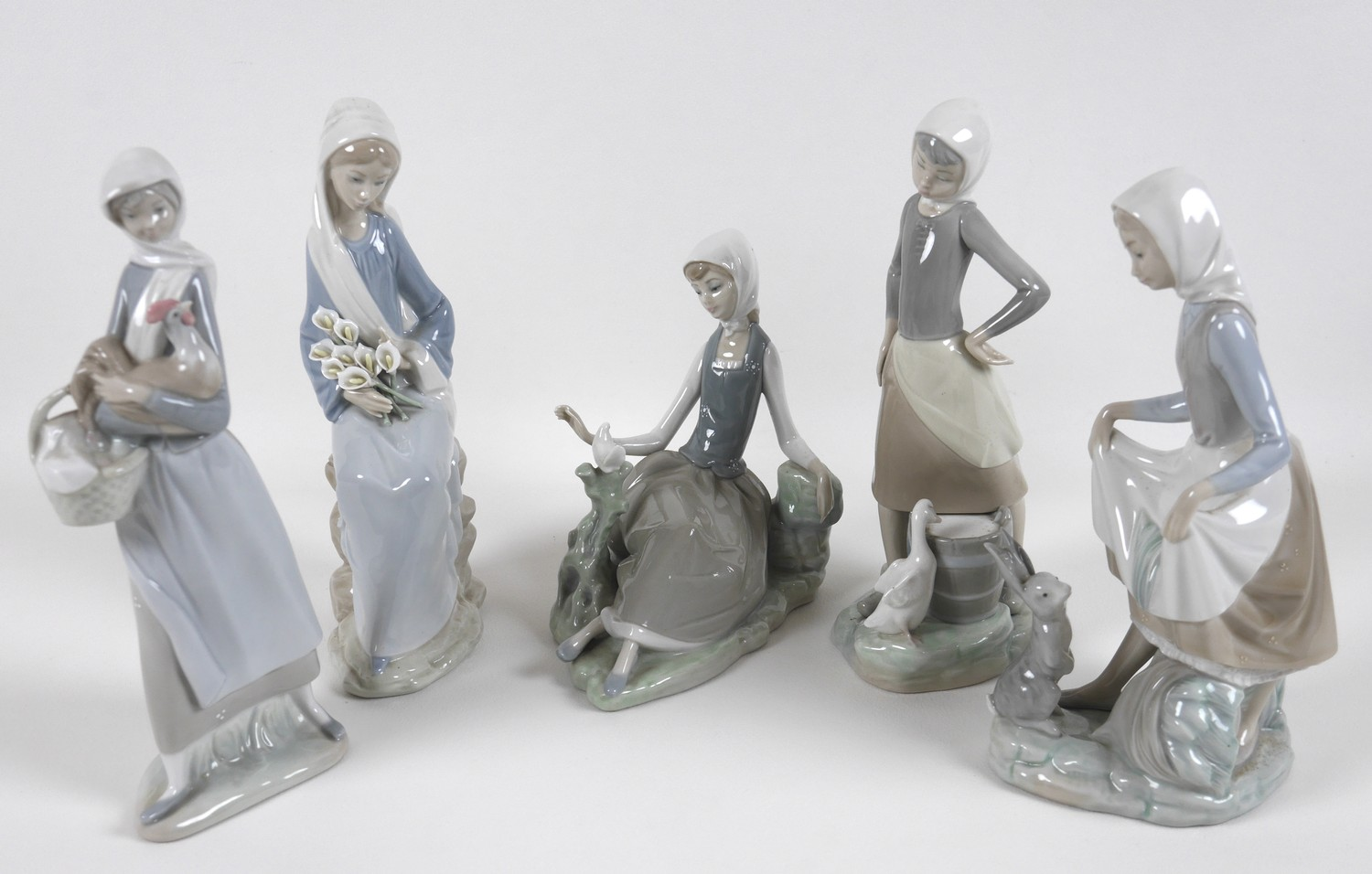 A group of five Lladro figures, comprising Armful of Lilies, number 4972, 24cm high, Peasant Girl