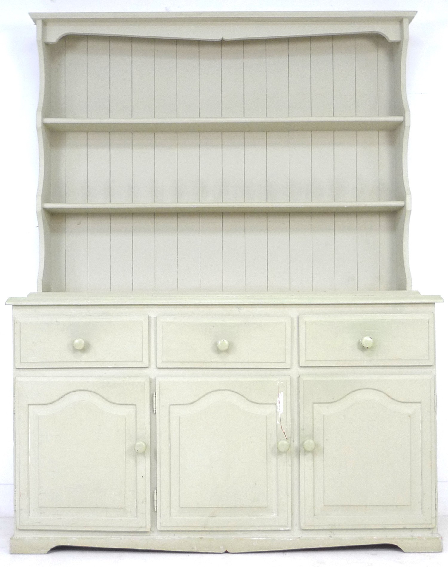 A modern pine pale green painted dresser, with plate rack over three drawers and three cupboards