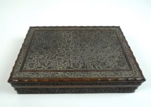 An Edwardian carved wooden box, decorated throughout with scrolling foliage and arabesques, with