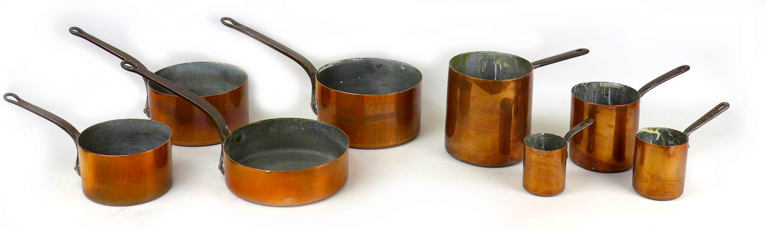 A group of eight 19th century copper saucepans, comprising two sets of four in graduating sizes,