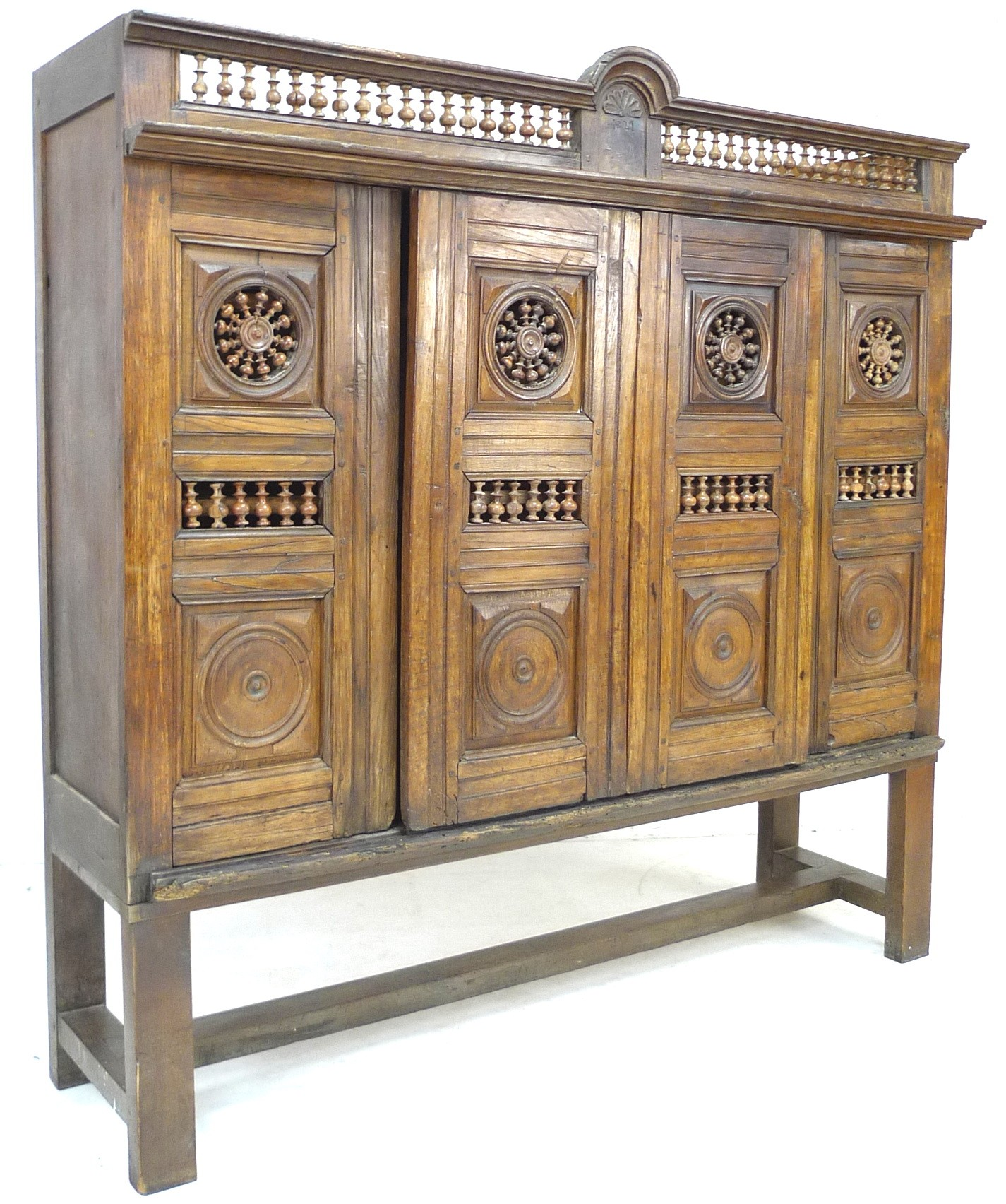 A French oak cupboard, 19th century and later, with carved and baluster detail, bears carved date '