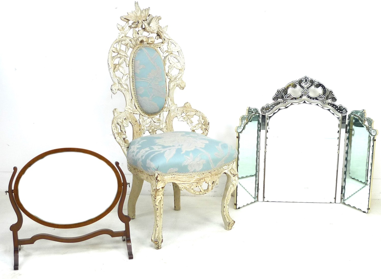 A Victorian nursing chair with cream painted carved frame, raised on cabriole legs to the front