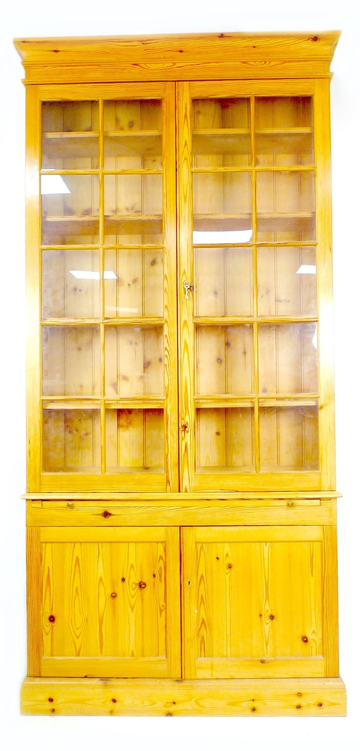 A modern pine bookcase, twin glazed doors, each with ten panes, enclosing four shelves, slide with