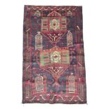 A dark blue ground Old Beluchi rug, decorated with architectural designs, 134 by 82cm.