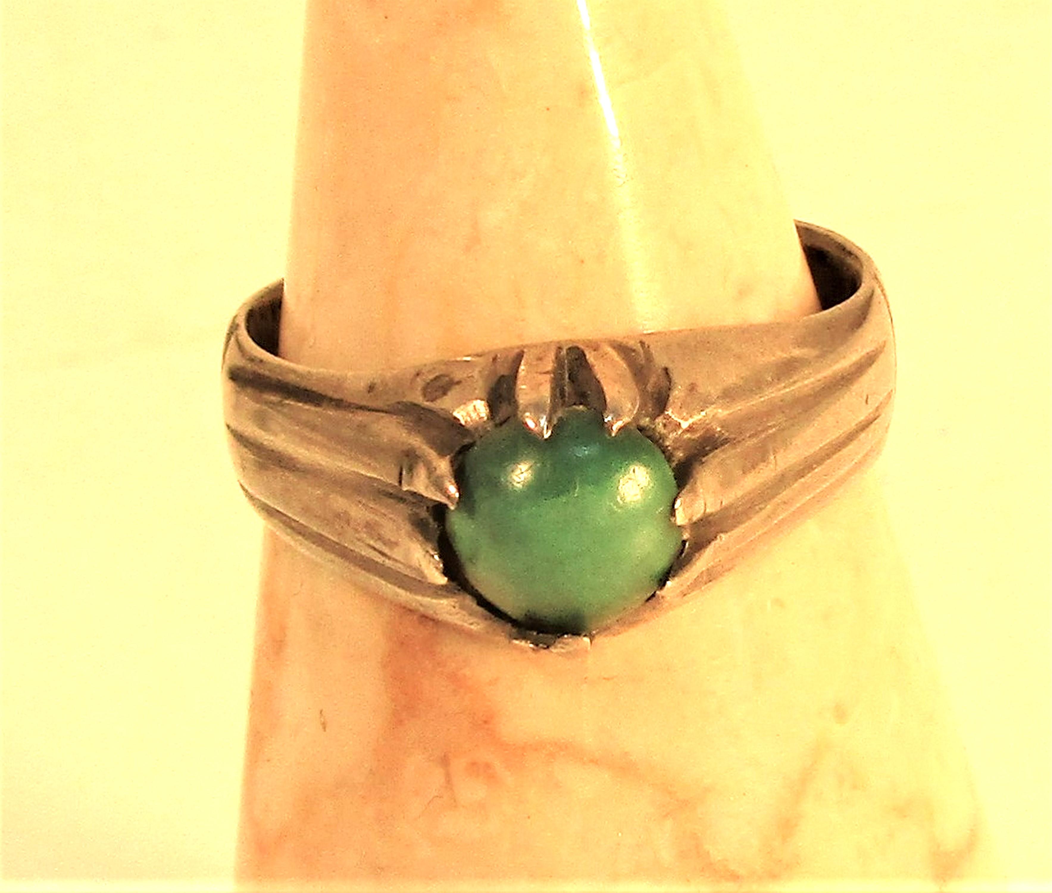 Light turquoise stone set in white metal ring.