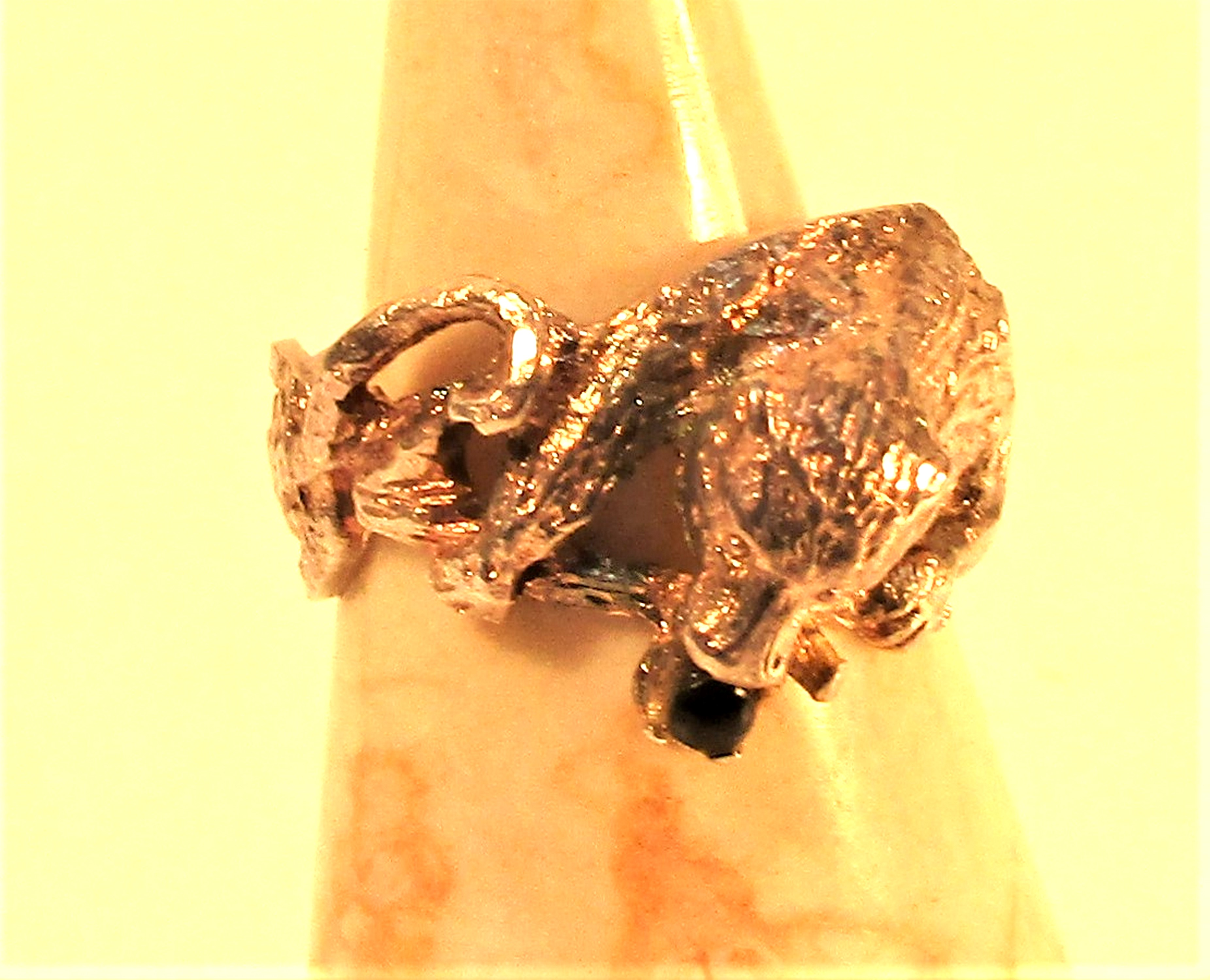 Cast white metal ring of a bear with a garnet