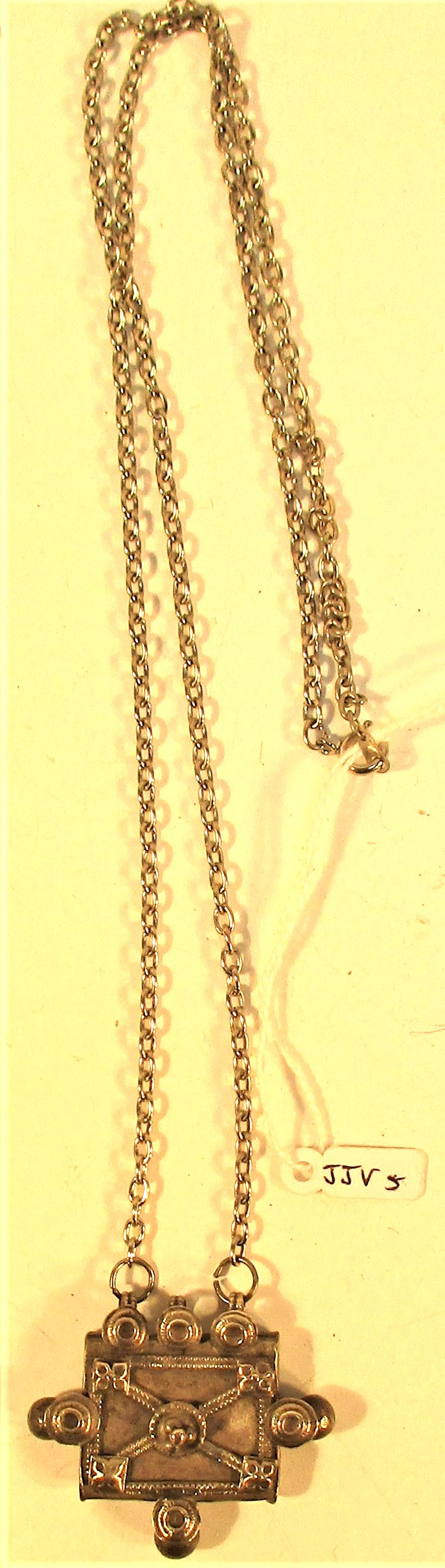 A pendant of an antique white metal amulet from Afghanistan on a chain. 32cm.