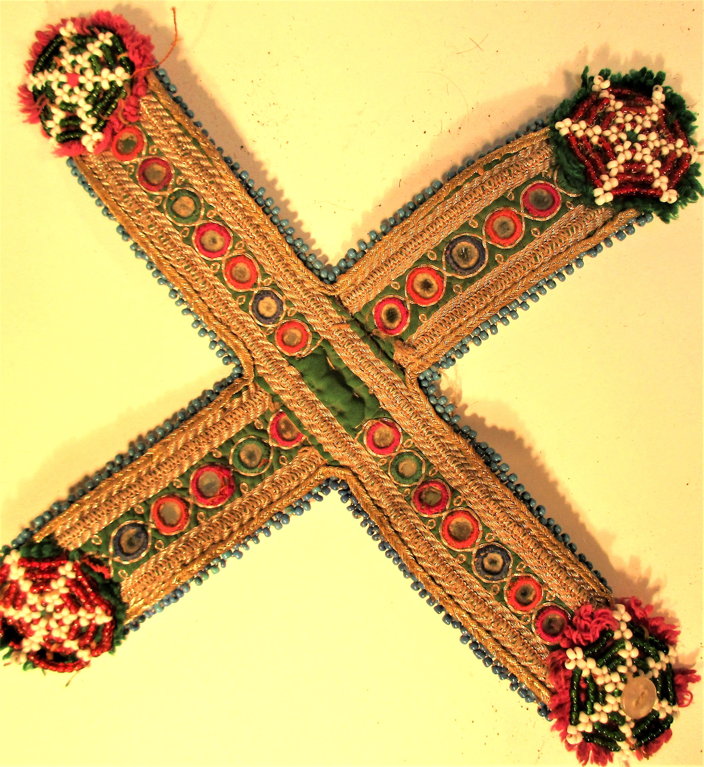 Dress decoration used by Koochi nomads. Embroidered gold wire, gul-i-perons and small mirrors. 20