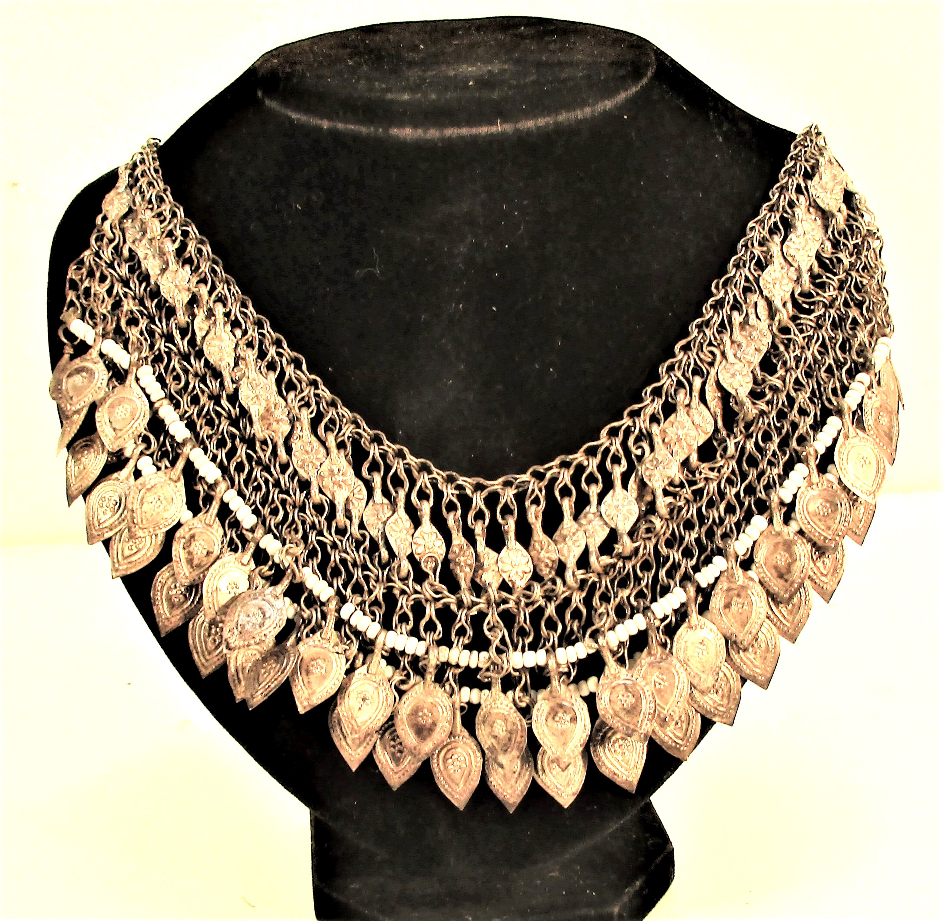 An elaborate Koochi nomad necklace. Chain with metal oval drops and tiny white glass beads . 27cm.
