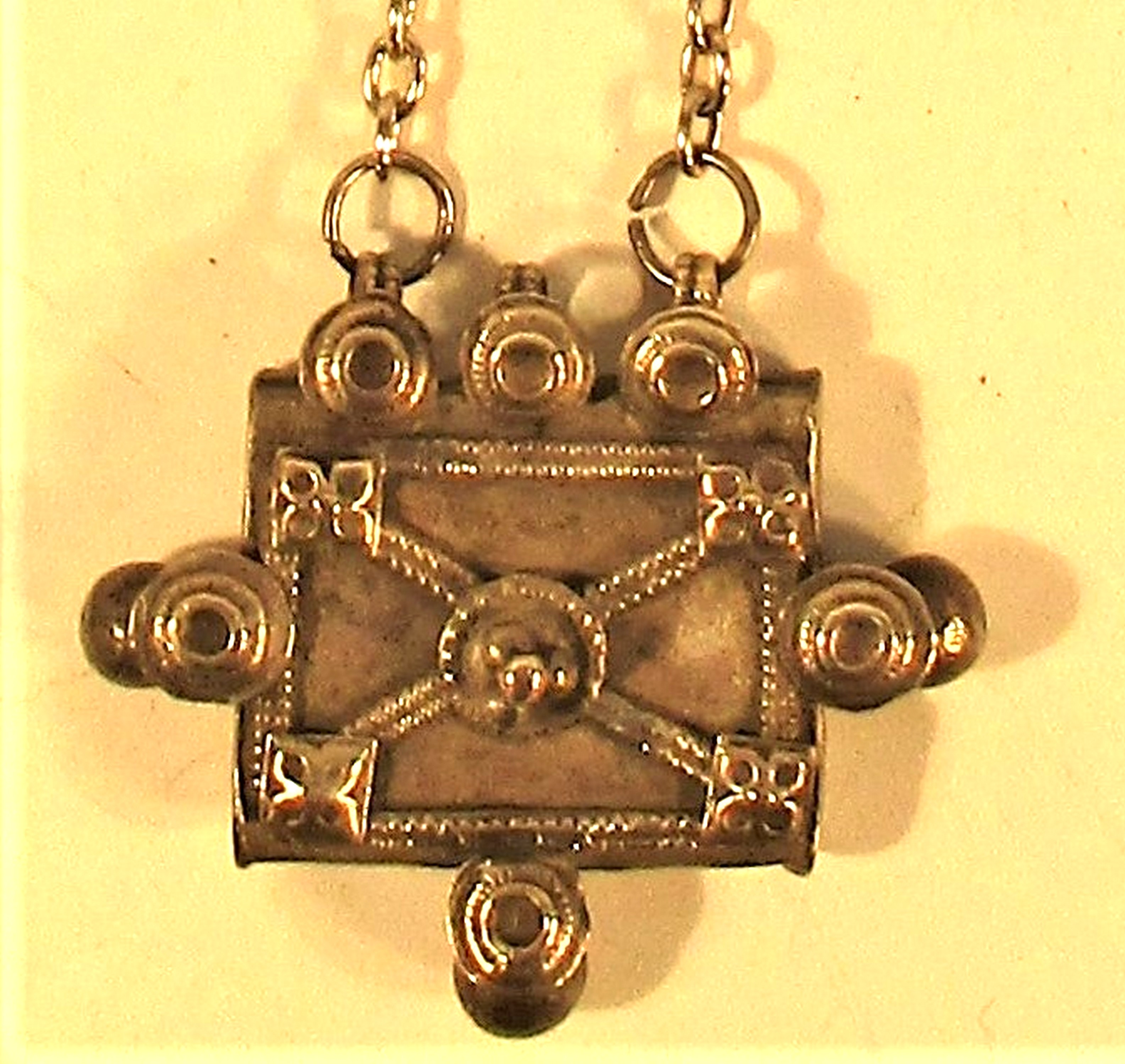 A pendant of an antique white metal amulet from Afghanistan on a chain. 32cm. - Image 2 of 2