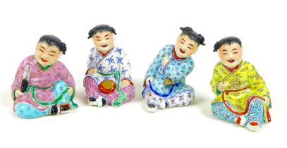 A group of four Chinese figures, late 20th century, each modelled as a seated child, smiling