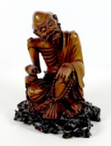 A Chinese carved wooden sculpture, late 19th / early 20th century, modelled as a mendicant, seated