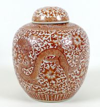 A Chinese ginger jar and cover, decorated in iron red with a dragon flying amongst a scrolling