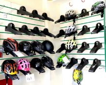 A group of fourteen helmets, various sizes and colours, together with thiry two slatwall mounting