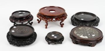 A group of six Chinese circular wood stands, 19th/20th century, one with inset marble top,
