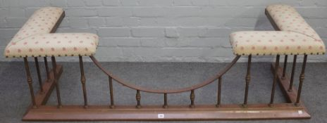 An early 20th century brass and cream upholstered club fender with sloped curb,