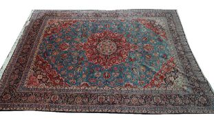 A Kashan carpet, Persian, the pale indigo field with a bold madder medallion, matching spandrels,