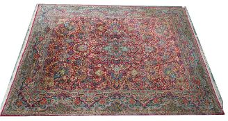 A Kerman carpet, Persian, the madder field with a central medallion, vase spandrels,