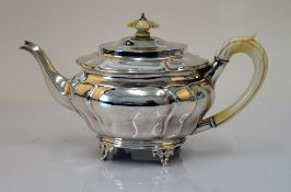 A silver teapot, of panelled oval form, raised on three feet,