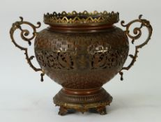 A late 19th century twin handled, gilt metal and copper jardiniere, of baluster form,