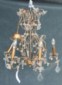 A 20th century gilt metal and glass six light chandelier, with scrolling branches and faceted drops,