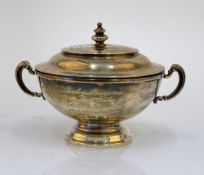 A silver twin handled bowl and cover, of circular form, raised on a circular foot,
