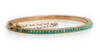 A gold and turquoise set oval hinged bangle,