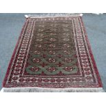 A Turkman rug, the washed sage field with three columns of nine guls; an ivory border,