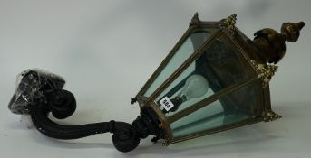 A Victorian hexagonal brass lantern, with glazed sides, supported on a scrolling wall bracket,