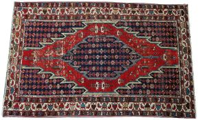 A Mazlaghan rug, Persian, the madder field with a serrated indigo medallion,