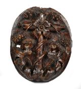 A 17th century Italian walnut oval panel relief carved with a fruiting vine,