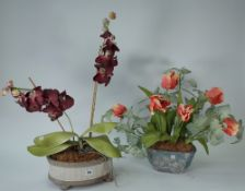An oval glazed pottery jardiniere containing artificial moth orchids,