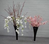 A pair of modern tall black glass tapered vases containing artificial tiger orchids and blossom,