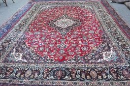 An Isfahan carpet, Persian, the madder field with a bold black and ivory medallion,
