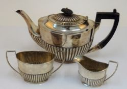 A silver composite three piece tea set, comprising; a late Victorian teapot with black fittings,