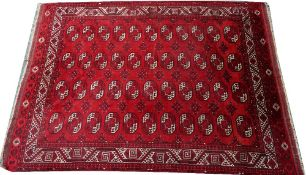 An Afghan carpet, the madder field with four columns of eleven single medallions,