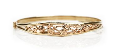 A 9ct two colour gold Welsh oval hinged bangle, pierced with foliate decoration,