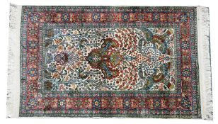 An Indian silk rug, the indigo field with a vase rising to two flying birds, floral sprays,