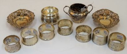 Silver, comprising; a pair of napkin rings decorated with floral moulded rims, Birmingham 1911,